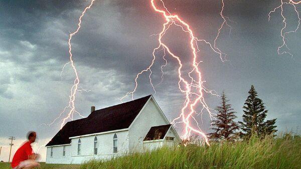 Молодой человек наблюдает за молниями во время грозы в Канаде