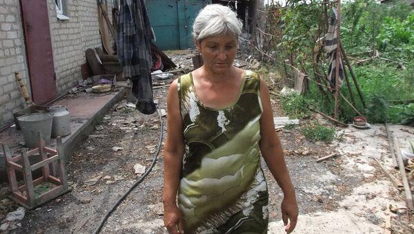 Женщина у дома, поврежденного в результате обстрела украинскими силовиками, в селе Саханка Донецкой области