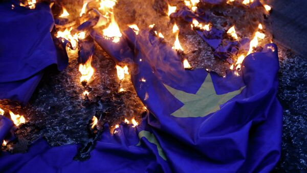 Демонстранцы жгут флаг на акции протеста против принятия проекта соглашения ЕС в Афинах. Архивное фото