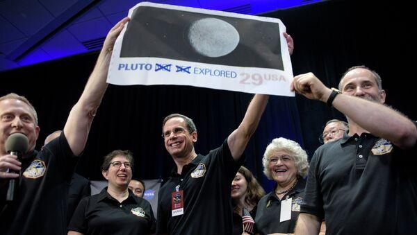 Доктор Аллан Стерн главный исследователь миссии New Horizons к Плутону с снимком планеты в Лаборатории прикладной физики Университета Джонса Хопкинса