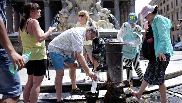 Туристы и жители Рима наполняют бутылки водой в жару. Архивное фото