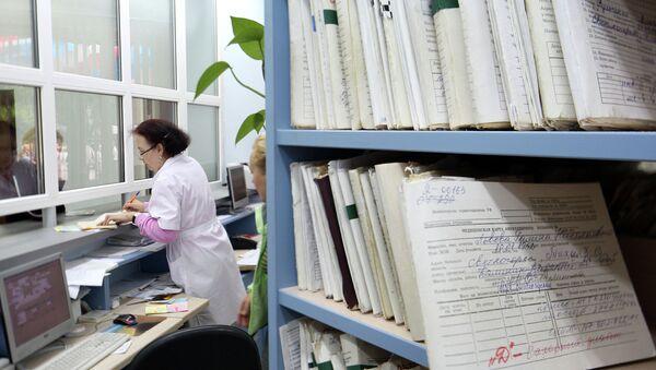 Медицинский работник выдает медицинскую карту пациенту в регистратуре поликлиники. Архив