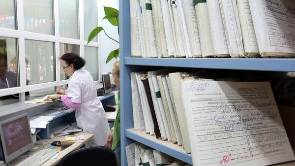Медицинский работник выдает медицинскую карту пациенту в регистратуре поликлиники