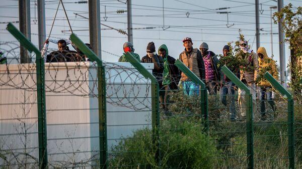 Мигранты возле терминала Евротуннеля во французском городе Кале