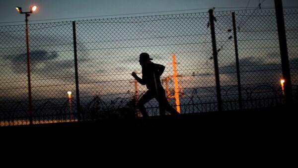 Мигрант пытается проникнуть в Евротуннель в Кале на севере Франции. Архивное фото