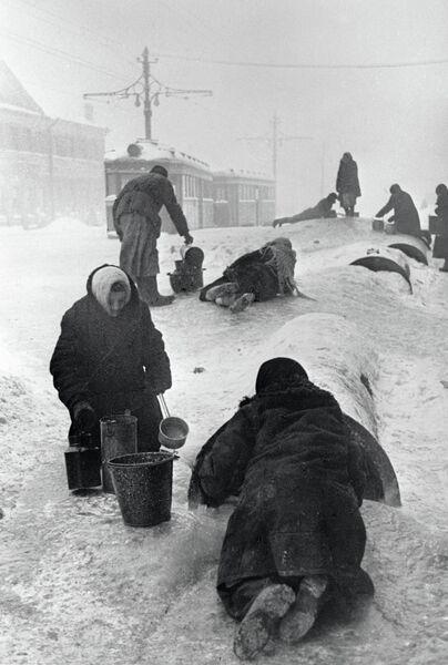 Жители блокадного Ленинграда набирают воду из разбитого водопровода на обледенелой улице