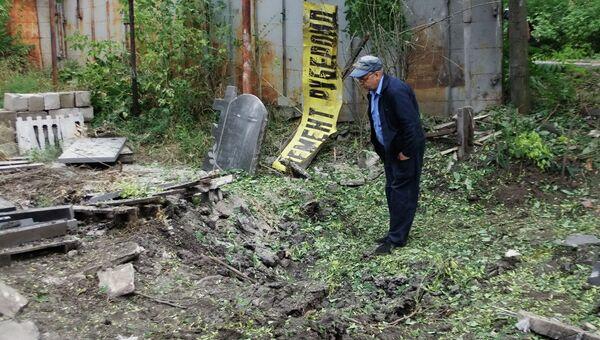 Мужчина рассматривает воронку от разорвавшегося снаряда в результате обстрела Донецка. Архивное фото