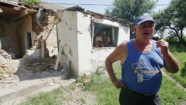 Житель деревни Новомарьевка на фоне разрушенного дома