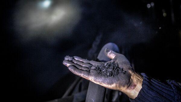 Шахтер показывает уголь на шахте. Архивное фото