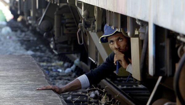 Мигрант под поездом до Сербии, на железнодорожном вокзале в Македонии. Август 2015