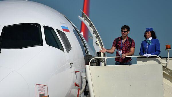 Посетители выставки осматривают самолет Sukhoi Superjet 100