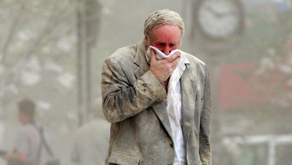 Мужчина идет среди обломков рухнувшей башни Всемирного торгового центра в Нью-Йорке. 11 сентября 2001 года