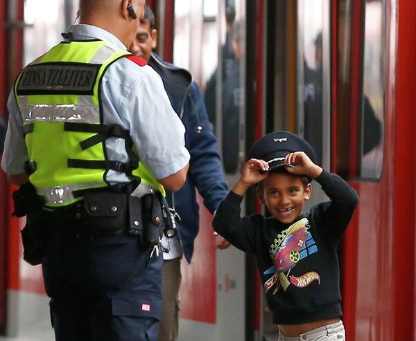 Мальчик из семьи мигрантов в фуражке сотрудника безопасности железной дороги Германии на станции в Мюнхене