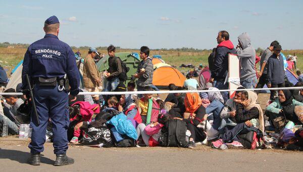 Венгерские полицейские встречают беженцев, заходящих на территорию Евросоюза в Венгрии в районе села Рёске