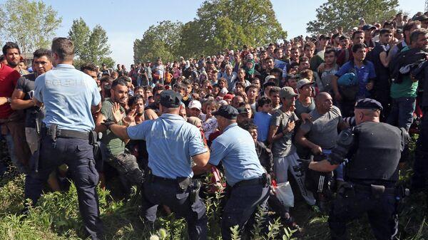 Беженцы пытаются пересечь полицейский кордон в Хорватии. Архивное фото
