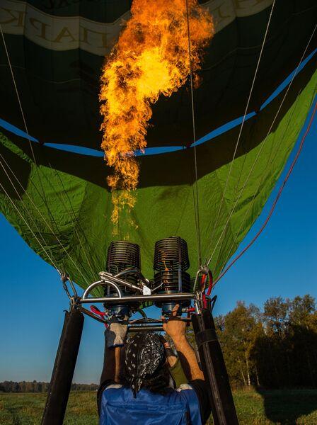 Нагревание воздуха в куполе воздушного шара при помощи горелки во время занятий воздухоплаванием в Московской области