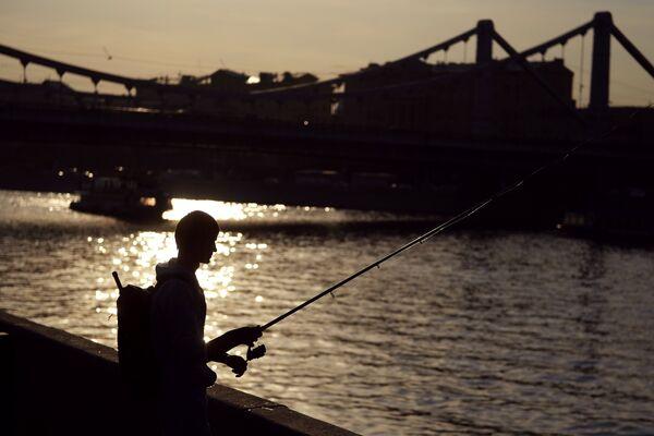 Молодой человек рыбачит в Москве