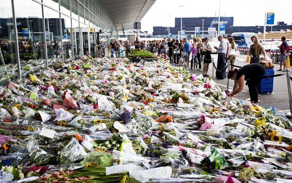 Люди возлагают цветы возле входа в аэропорт Схипхол, Нидерланды