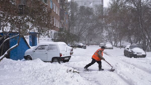 Сотрудник коммунальных служб убирает заснеженные улицы города Омска