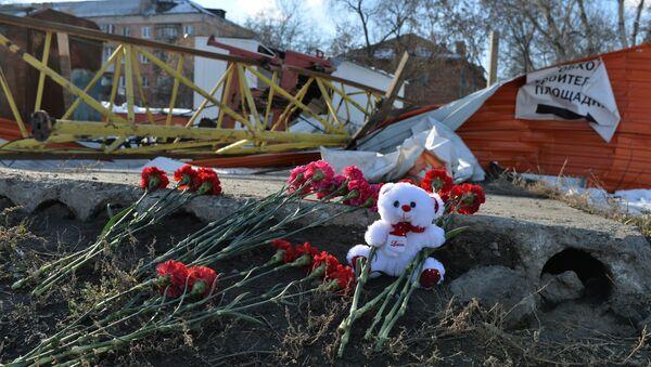 Цветы на месте падения башенного крана в Омске, в результате которого погибли четыре человека