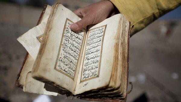 Ребенок держит сборник мусульманских молитв, найденный в разрушенном в результате авиаударов доме в Сане, Йемен