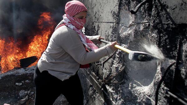 Палестинская женщина пытается разрушить разделительную стену на Западном берегу Абу-Дис