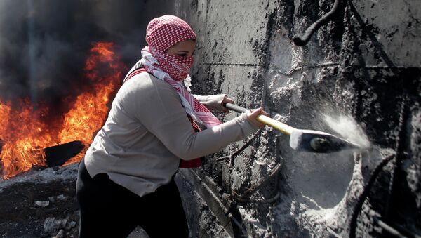 Палестинская женщина пытается разрушить разделительную стену на Западном берегу Абу-Дис. Архивное фото