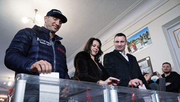 Лидер объединенной партии Солидарность, мэр Киева Виталий Кличко с супругой Натальей и его брат Владимир Кличко (справа налево) на избирательном участке в Киеве во время второго тура выборов в органы местного самоуправления.