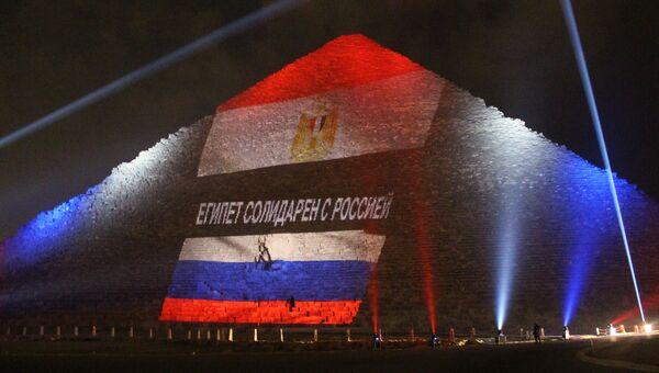 Древнеегипетская пирамида Хеопса на плато Гиза в Каире, подсвеченная цветами российского и египетского флагов во время акции памяти жертв. Архивное фото