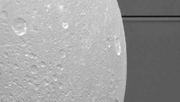 Крупный портрет Дионы на фоне колец Сатурна
