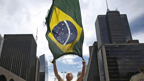 Мужчина размахивает флагом Бразилии во время акции протеста в Сан-Паулу