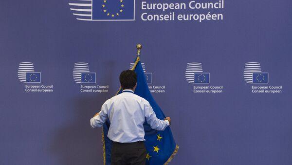 Служащий поправляет флаг в здании Совета Европы в Брюсселе, Бельгия