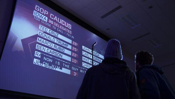 Люди смотрят результаты первичного голосования в Айове