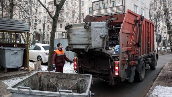 Сотрудник коммунальных служб выгружает мусор из контейнера в мусоровоз