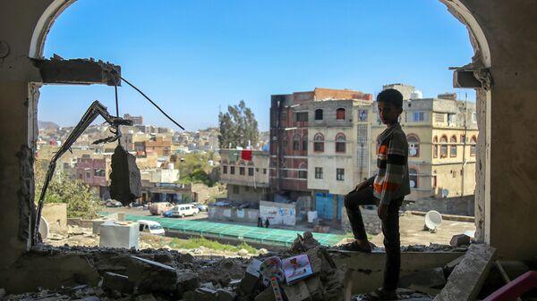 Мальчик осматривает разрушенное здание после атаки на город Таиз в Йемене. Архивное фото