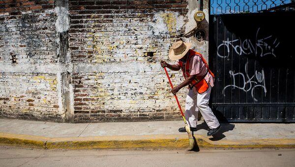 Муниципалитет работник подметает тротуар во время очистки города в Мексике