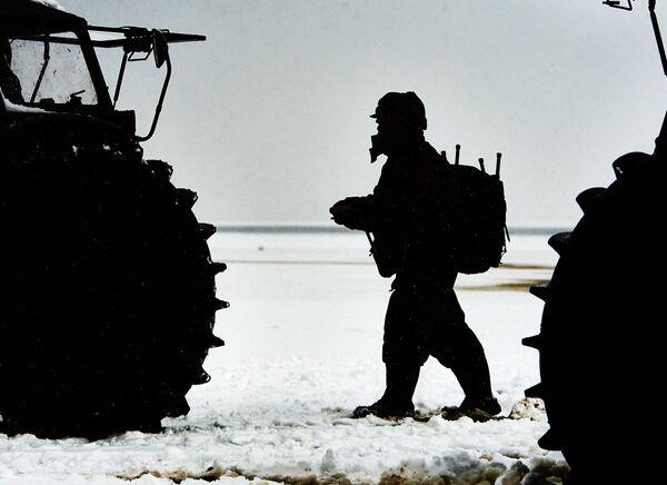 Рыбак осматривает отечественный вездеход-амфибия Шерп на берегу Ладожского озера в Ленинградской области