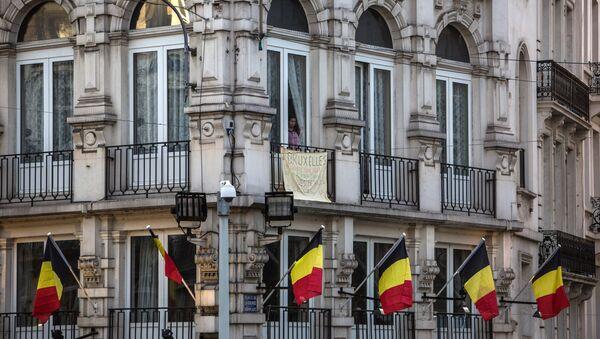 Мужчина в окне здания на Биржевой площади в Брюсселе