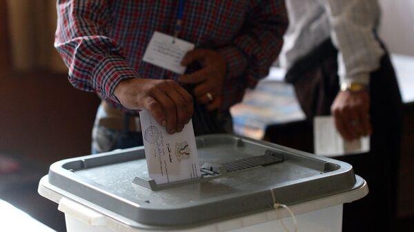 Мужчина опускает конверт с бюллетенем в урну на одном из избирательных участков во время голосования на парламентских выборов в Сирии