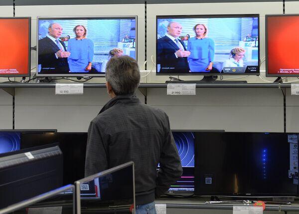Посетитель магазина М-видео смотрит трансляцию ежегодной специальной программы Прямая линия с Владимиром Путиным
