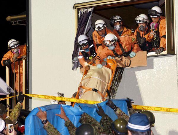 Спасатели выносят женщину из разрушенного в результате землетрясения дома. Кумамото, Япония. Апрель 2016