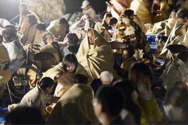 Местные жители сидят в одеялах на дороге после землетрясения. Кумамото, Япония. Апрель 2016