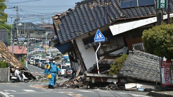 Полицейский среди разрушенных в результате землетрясения зданий в Кумамото, Япония