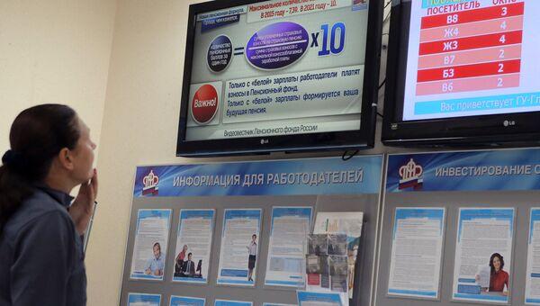 Посетитель читает информацию в Главном Управлении Пенсионного фонда РФ № 8 города Москвы и Московской области. Архивное фото