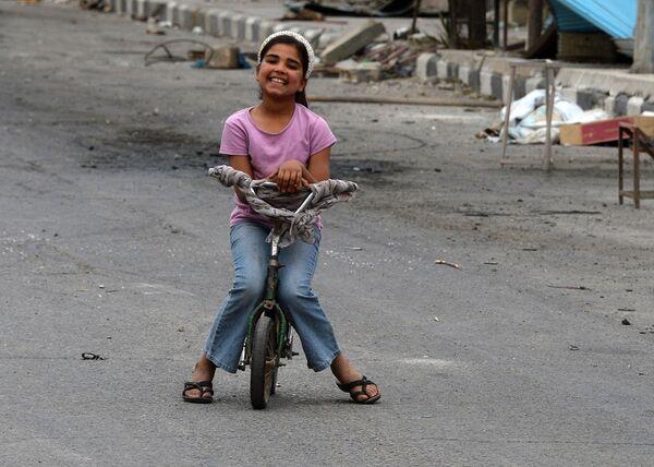 Девочка катается на велосипеде по одной из улиц Пальмиры