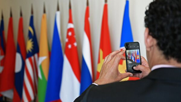 Участник саммита Россия — АСЕАН фотографирует флаги в конгресс-центре в Сочи