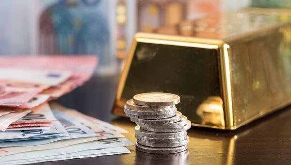 Слиток золота, монеты и банкноты евро. Архивное фото
