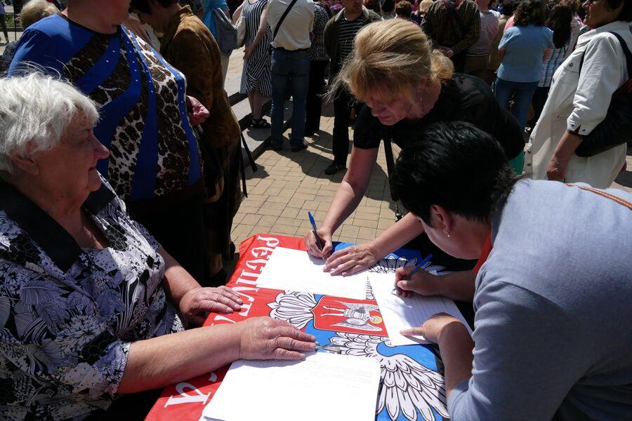 Жительница Донецка во время митинга подписывает петицию против нарушения Киевом резолюции Совета Безопасности ООН