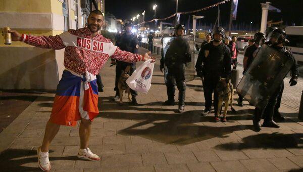 Российский болельщик возле полицейских на одной из улиц Марселя после окончания матча между сборными командами Англии и России