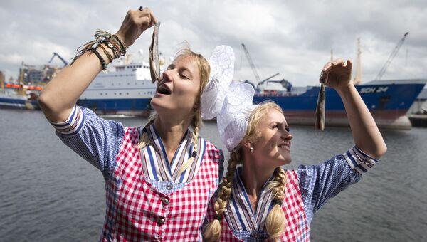 Модели позируют с селедкой после аукциона в порту Схевенинген